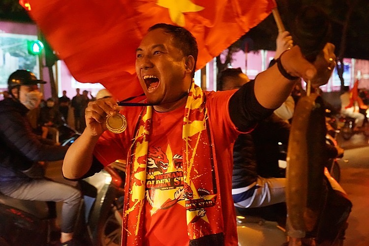 A Hanoi fan screams with joy, showing his handmade gold medal. Photo by VnExpress/Gia Chinh