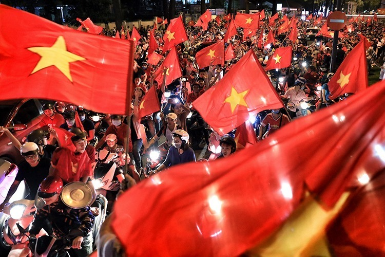 Fans flood the street of Saigon on motorbikes, waving the national flag. Photo by VnExpress/Huu Khoa.