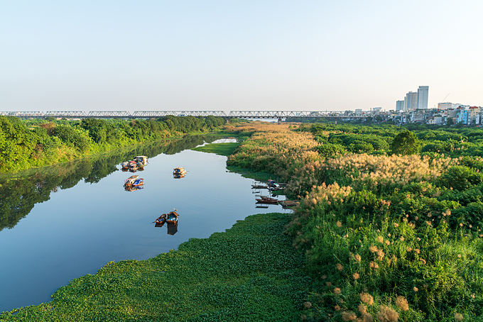 Life on the Red River bank is viewed from Long Bien Bridge in Hanoi. Photo by Shutterstock/ Ha Anh.