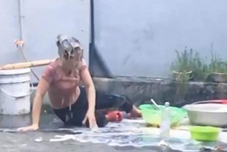 A mother falls when her son pours egg yolk on her from a balcony. A screenshot from the video.