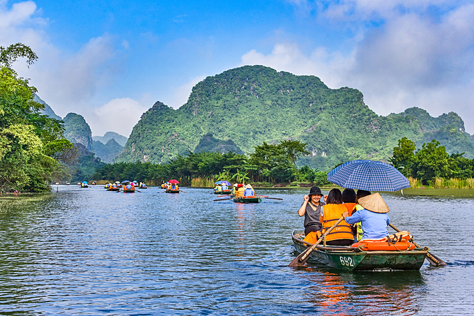 Trang An limestone landscape is famous for boat cave tours that attract millions of tourists every year. Photo by Shutterstock/Anh Tran.