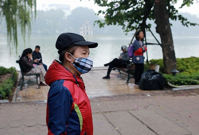 A woman wears a mask while walking at the Hoan Kiem (Sword) Lake area.