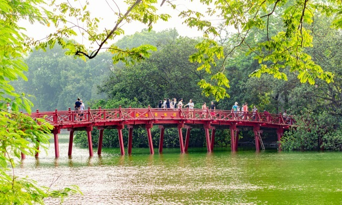 Tourists visit The Huc Bridge that connects Ngoc Son Temple to the banks of Hoan Kiem (Sword) Lake in Hanoi. Photo by Shutterstock/Jimmy Tran.