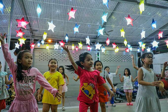 At the communal house in Binh Thuan church in District 8, children rehearse their Christmas carols and dances for a performance on Christmas night.