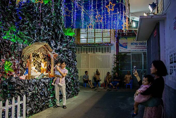 A father and daughter pose by a Christmas decoration in Dat Thanh street in Tan Binh District. Dat Thanh means the land of saint.