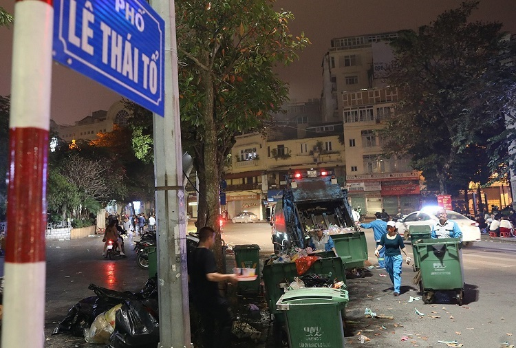 Waste workers collect waste on Le Thai To Street at 2 a.m. on Wednesday.