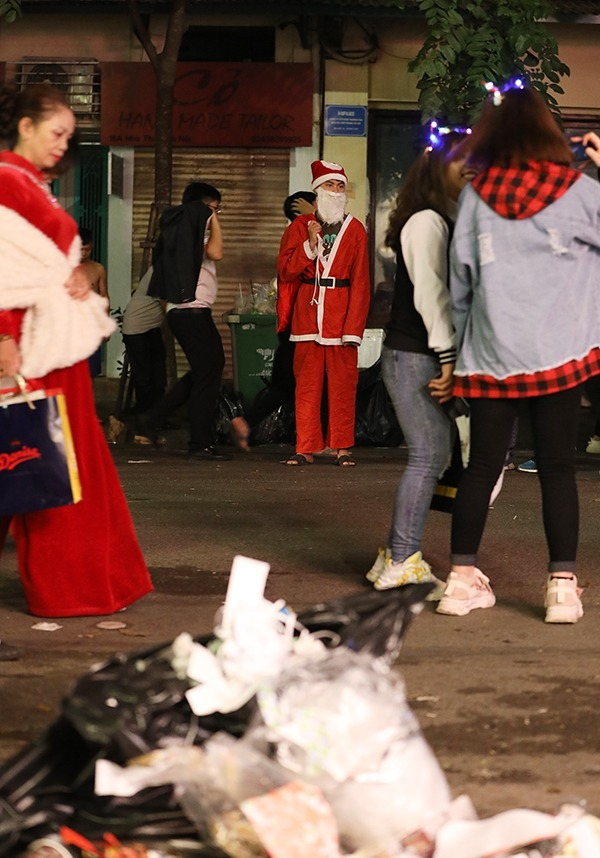 A man in Santa Claus costume stands by the Church Street that leads straight to the cathedral. A garbage bag can be seen in front of him while a full trash bin surrounded by bags of trash is right behind him.