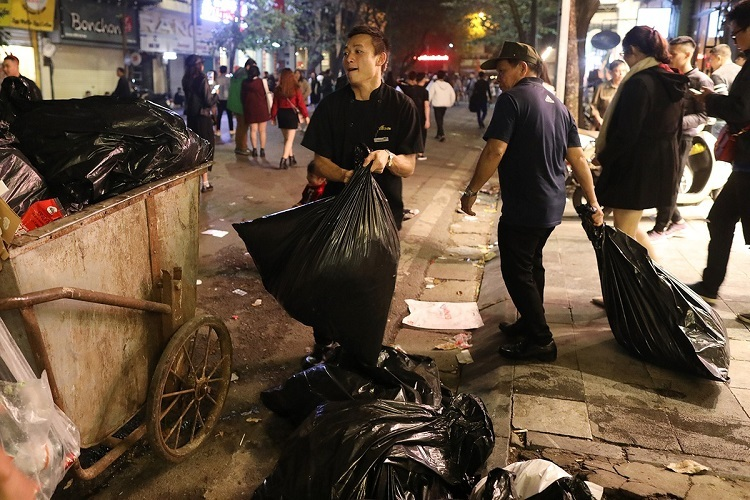 Staff of a restaurant carry bags of waste to wagons of waste collectors.