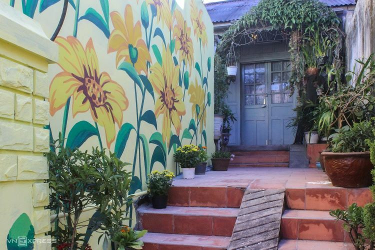 Murals depicting, amongst others, Mexican sunflowers, Da Lat train station or its Cathedral bell tower span the length of the street, covering several private homes and public space alike.