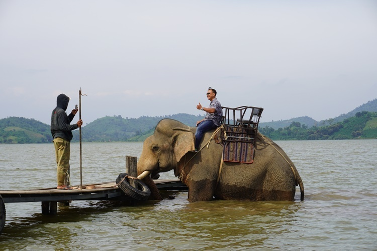 A tourist poses for a picture taken by a mahout atop an elephant in Lak district, Dak Lak Province. Photo by VnExpress/Tran Hoa
