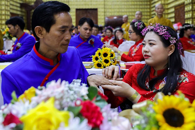Phi Hung, 47 (L) and Hong Nhiem, 31 exchange rings in their wedding ceremony. The couple has been together for 10 years and has a 9-year-old daughter.Both os us have defects in our legs. [Hung] is worse off than me because he doesnt have his parents. Lives as manual workers are tough, so we didnt dare to have a wedding, said Nhiem.