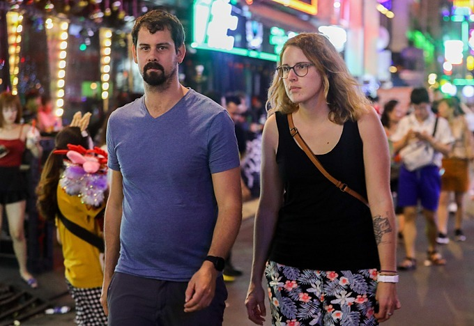 A foreign couple walk on Saigons Bui Vien Street in HCMC. Photo by VnExpress/Quynh Tran.