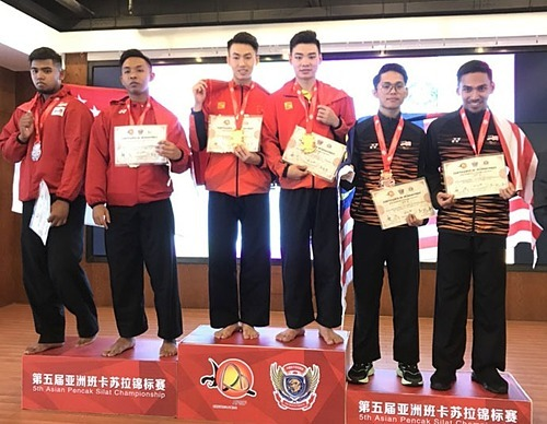 The Vietnamese men (C) who won the two-athlete artistic performance contest at the 5th Asian Pencak Silat Championship receive their gold medals in Yajin, China. Photo by Hanoimoi/Thu Huong.