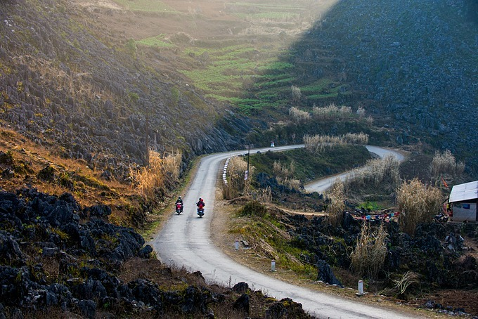 Tourists drive their motorbikes through rugged and dangerous roads in Ha Giang. Photo by Shutterstock/Hoang Anh.