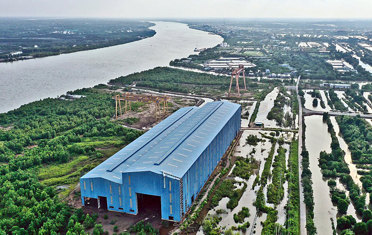 With VND1 trillion ($43.2 million) invested by Vietnam Shipbuilding Industry Group (Vinashin), a debt-ridden state-owned giant embroiled in embezzlement scandals in the late 2000s, a shipyard was built in 2008 on the banks of Cai Lon River, Xom Trong Hamlet, Hang Vinh Commune, Nam Can District, Ca Mau Province in southern Vietnam.With the projected capability of employing 4,000 workers to manufacturing ships of up to 10,000 tons, the facility was built across 58 hectares of land acquired from 127 local families.However, the project was kickstarted during the 2008 global economic depression that saw great drops in the demand for new ships. Thus, despite being completed, the yard has never been used.