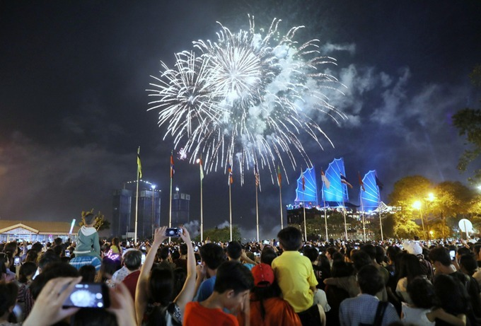 People use their smartphones to catch the sparkling moment of fireworks lighting up the sky at Bach Dang Wharf in downtown area. Photo by Huu Khoa.