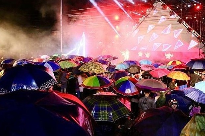 [Caption]Locals in Quang Binh, home to the UNESCO heritage site Phong Nha-Ke Bang in central Vietnam, carrying umbrellas stood in the rain at an outdoor stage to watch a music program to welcome the New Year.