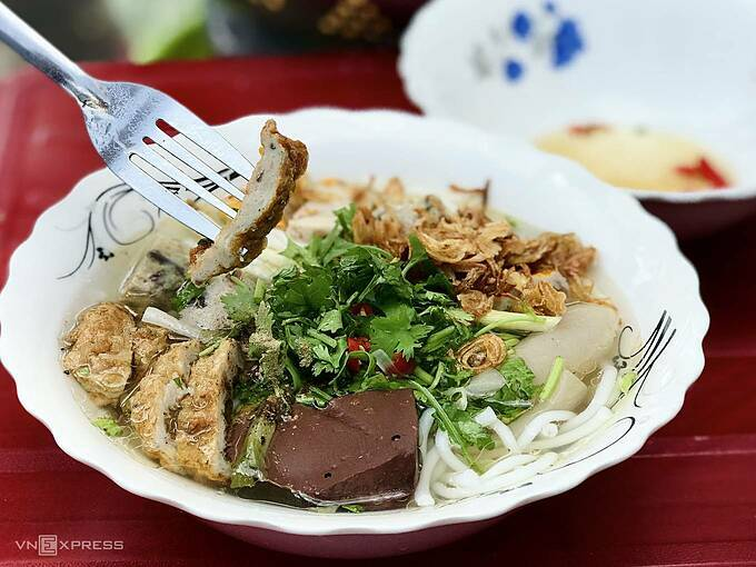 A Phan Thiet specialty, the dish uses fresh fish netted in Binh Thuan sea of Phan Thiet.The fish flesh is used to make cakes while the bones are stewed along with pork bones to make the broth flavorful. An all-ingredient bowl consists of noodles, fish cakes, pork ears, pork cakes, and pig blood, cilantro, green onion, and black pepper. The dish is served hot and presented in an eye-catching manner.You can find the dish at markets and many sidewalk stalls in Phan Thiet for about VND15,000 - 35,000 a bowl ($0.65-1.5)Some local recommendations are Xiu stall at 1 HA Kim Dong Street, (Kim Dong street), Ms. Lys stall at 566 Tran Hung Dao Street and Ms. Dungs stall at the intersection of Vo Thi Sau and Ton Duc Thang streets.