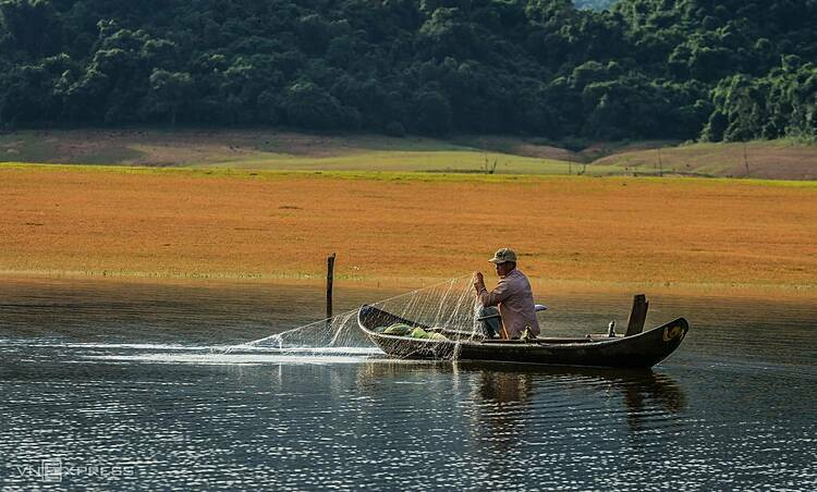 A fisherman and his net in the shrunken lake during the dry season.