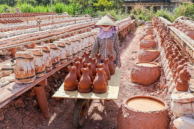 A worker brings the ceramic mice into the kiln.