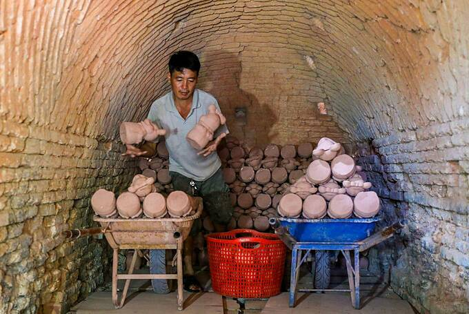 Hop's husband Le Quang Loi, 48, arranged the products in the kiln. They need to be heated for about 10 hours. On average, a kiln can hold 3,000 products a day, Loi said.