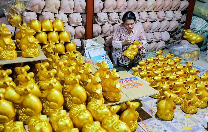 After the hardening process, the bisques are brought to workshops in Thuan An town in Binh Duong for decoration. Vo Thi Thanh Hang, 42 years old said about 2,000 products are brought here every day.  Hang paints each mouse in gold colour. The main commodity is still piggy bank because it is popular. This year, mouse is popular because of Tet, she said.