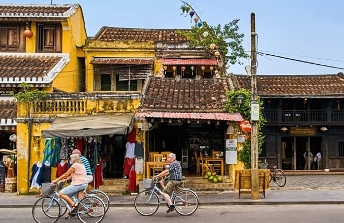 Foreign tourists ride their bicycles in the ancient town of Hoi An. Photo by Shutterstock/Huy Thoai.