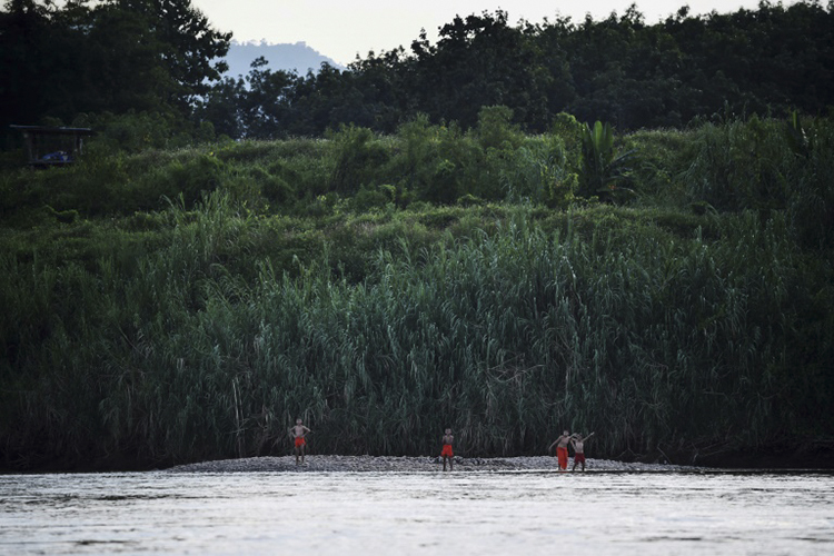 Novice Buddhist monks on a river bank along the Thai side of the Mekong River in the northern Thai province of Chiang Rai.