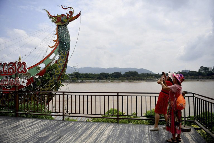 Chinese tourists taking pictures along the Mekong River from the Thai side of the Golden Triangle in Chiang Rai province September 19, 2019.
