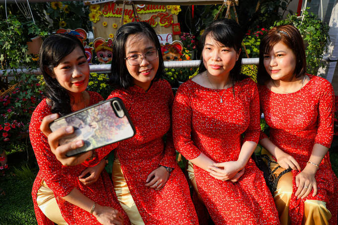 Doctors of the haematology department scheduled for a photo together at the flowery path with red Ao Dai, Vietnamese traditional dress.