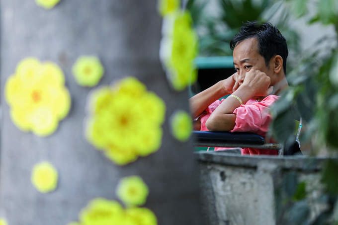 A patient having fresh air beside a blossom decoration.