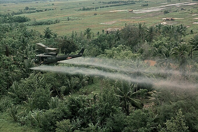 A helicopter from the 336th Aviation Company sprays chemical on a jungle area in the Mekong delta in Vietnam War. Photo by Shutterstock/Everett Historical.