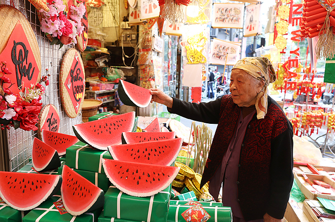 This year, handicraft items such as banh chung (square sticky rice cakes), Vietnamese pork sausage, coins, watermelon, firecrackers, fake peach branches are widely sold at shops.