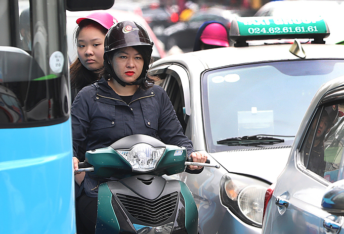 A woman tries to squeeze through long lines of vehicles on Dien Bien Phu Street.