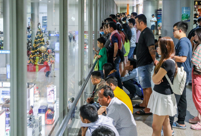 Trying to get rid of the crowd, people look for their family members and relatives through the glass window.The airport has beenexpected to get peak crowds between January 9 and February 8 as people travel forTet, the biggest holiday in Vietnam and main occasion for family reunions.