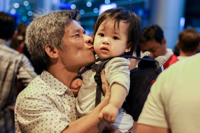 After two hours of waiting, Thanh (L) finally meets hisgrandaughter Kha Di and her parents visiting from Australia. The man maintains he has been waiting for Tet the whole year just to see his children.