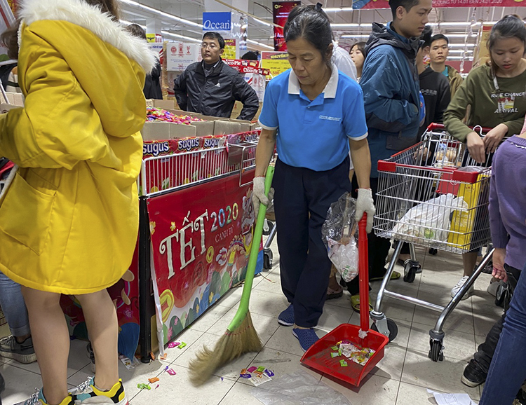 A sanitation worker cleans the floor as some customers have their snack right after buying and litter packages on the floor.