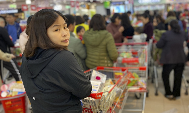 This woman says she has stayed in line for 20 minutes to reach the cash register counter, and will definitely have to wait longer since she is still standing behind many. The supermarket opens up to 60 counters but still could not meet the high demand.