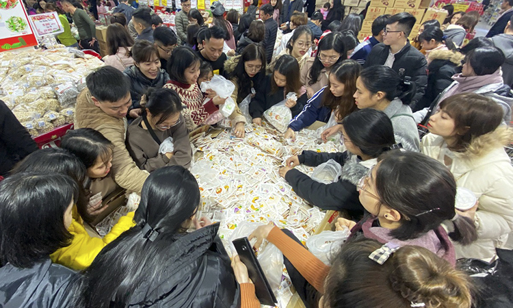 There is a scramble to but jelly candy (choose one), which costs VND50,000 (more than $2) per kilogram. Some buy 10 kg of it. A man says he was well aware the supermarket would be crowded but still prefers to shop there because prices of most products are cheaper than at other places. He buys confectionery in bulk and packs it in boxes to gift relatives.