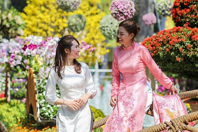 Two girls wearing traditional Vietnamese ao dai pose for a photo amidst the background of the vibrant flower scene.
