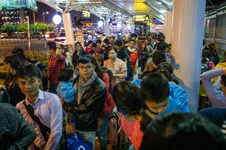 Around 15 columns of people nearly a kilometer long each, await their turn for security checks.