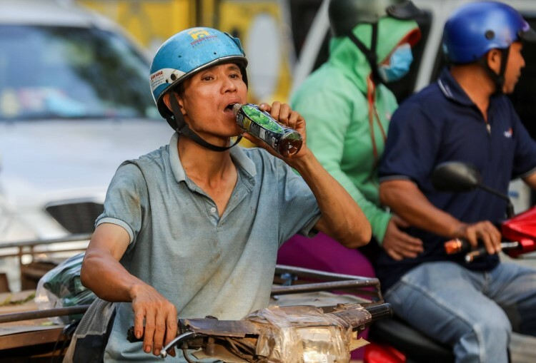 A deliveryman drinks in the middle of traffic.