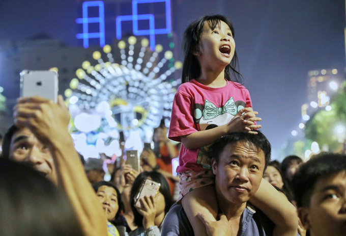 A girl being sitting on her father's shoulders reacted to the fireworks, which lasted for about 15 minutes. Photo by VnExpress/Quynh Tran