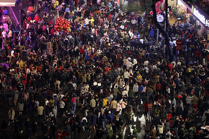 The rain did not stop thousands of residents to gather at Hoan Kiem Lake downtown to watch the fireworks. Photo by VnExpress/Ngoc Thanh.