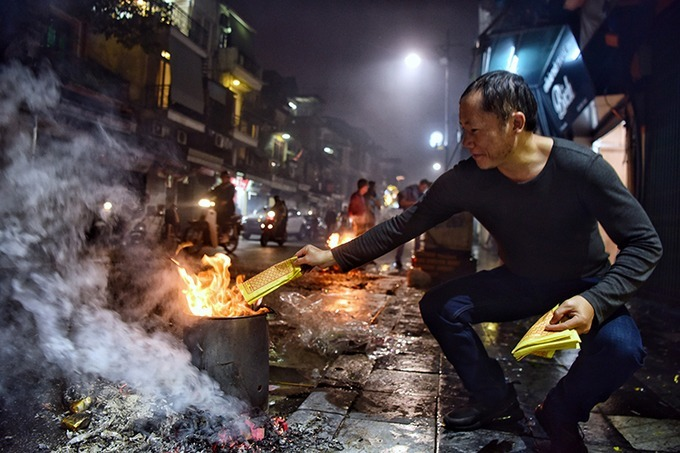 A man burnt joss paper. For many Vietnamese, burning joss paper symbolizes the quest for luck, health, and prosperity in the new year, the belief being that, when burnt, offerings would be delivered to the deceased. Photo by VnExpress/Giang Huy.
