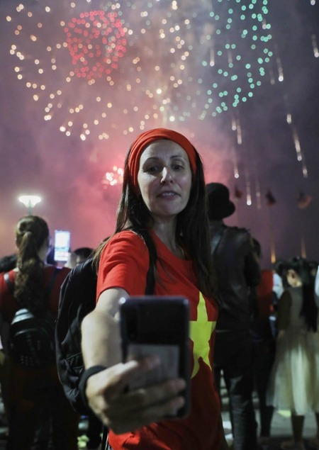A foreigner takes a selfie in with fireworks. Photo by VnExpress/Quynh Tran.