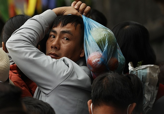 A man holding a nylon bag of fruits as offerings to the gods was stuck in long queues.