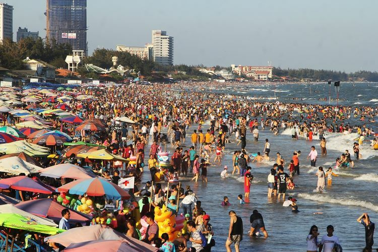 Thousands of sunbathers cram Bai Sau beach on Tuesday afternoon. As many as 10 km of coast is swathed with holiday-makers, with parks and touristic sites buckling under increased amounts of two-wheelers and cars.
