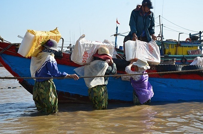 Women in Ngu Loc Commune, Hau Loc District, Thanh Hoa Province, carry huge ice blocks to boat. Photo by VnExpress/Nguyen Ngoan.