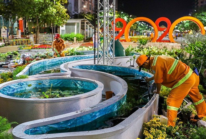 Workers remove the environment scene designed to highlight the need for recycling and waste treatment, water conservation, and forest protection. The cleaning of the flower street needs to be carried out synchronously such as cutting power first, clearing the flowers and then removing scaffoldings, said a worker identified as 45-year-old Van Tien.